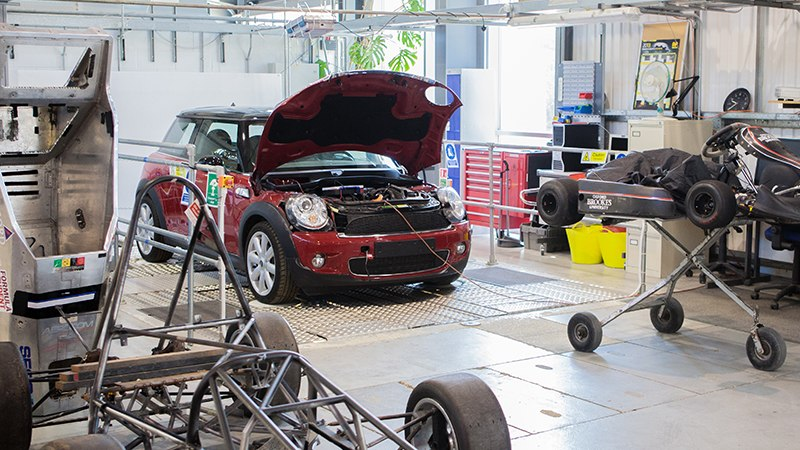A mini car with its bonnet open in a lab