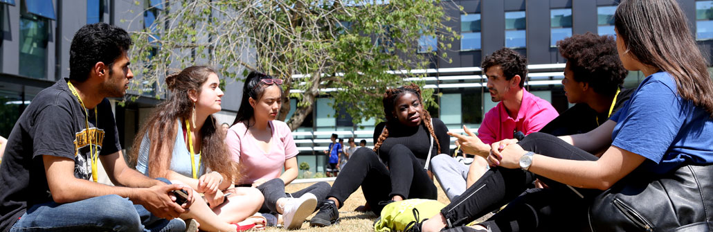 Students sitting on the grass on HEadington Campus