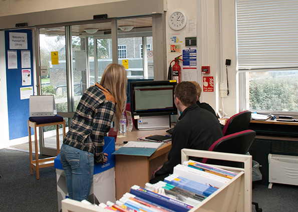 student being assisted by a member of staff in the Help Zone