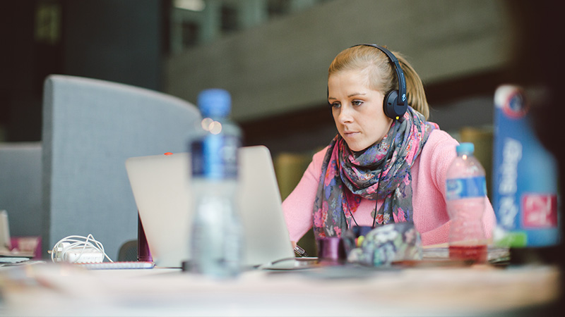 Female student studying on a laptop with headphones on