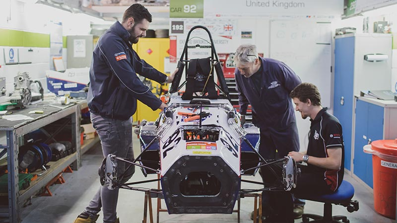 Students working on a motorsport car in garage