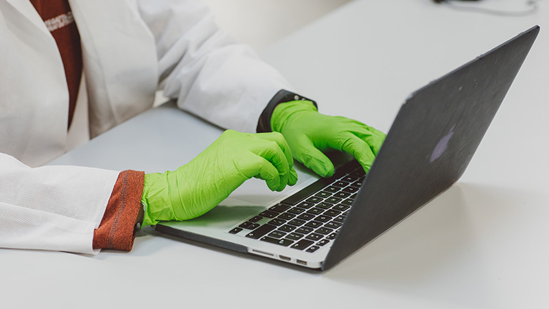 Student typing notes on a laptop in the lab