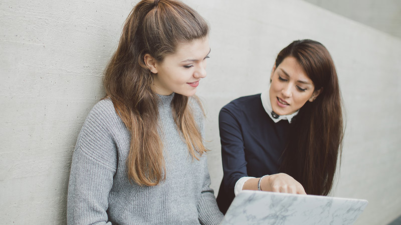Two female students discussing work on a laptop