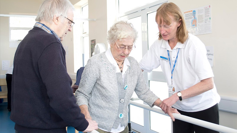 Healthcare professional aiding elderly patient to walk