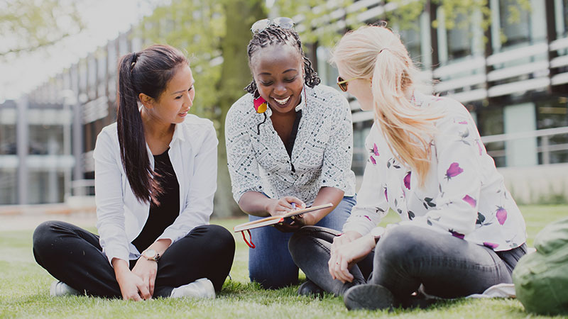 Three female students studying together outside