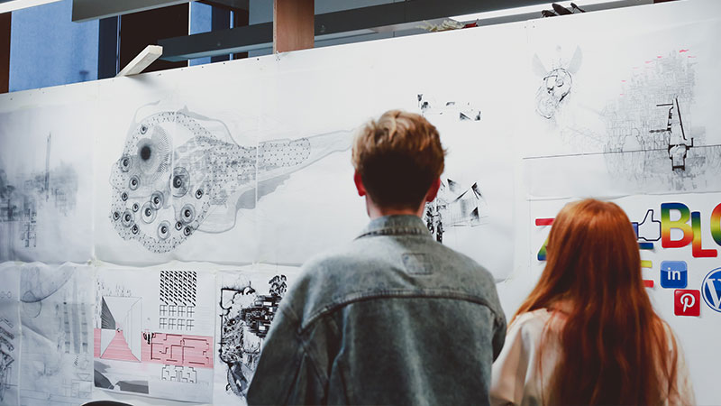 Two students looking at drawings fixed to wall