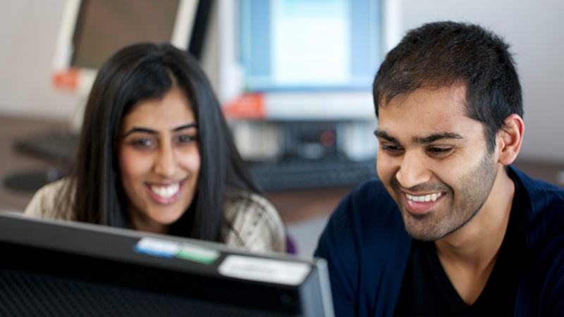 Female and male student working together on a computer