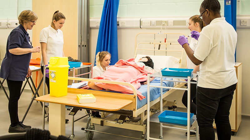 Nursing students in simulated practice with a manikin