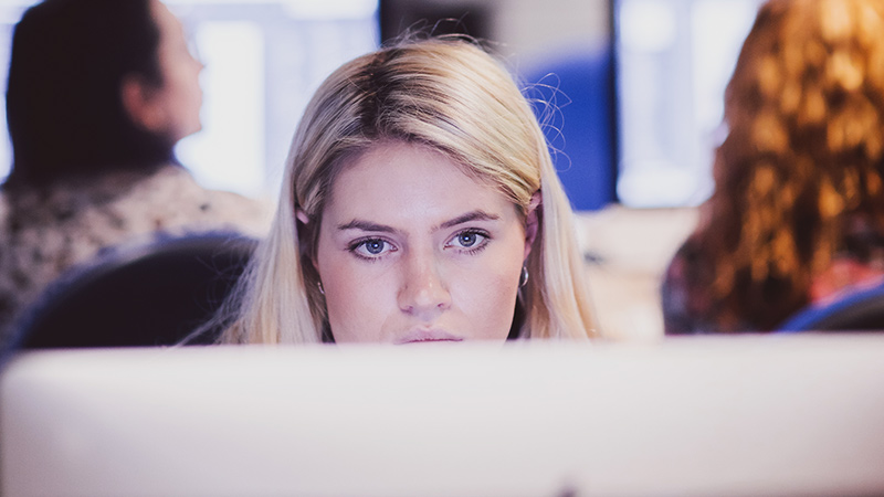 Female student looking at a desktop computer